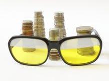 硬币和老牌太阳镜利益  免版税库存图片