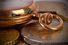 硬币和金黄怀表 免版税库存图片