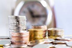 硬币在时钟背景堆积 免版税库存图片