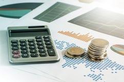 硬币堆和计算器在财政图表纸  事务 免版税库存图片