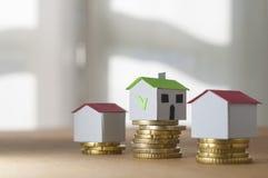 硬币堆的纸房子:抵押和贷款批准的概念 库存图片