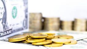 硬币堆积和在白色桌背景的美元钞票 库存图片