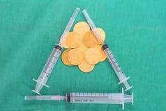硬币或金钱与多个注射器在手术绿色礼服cov 免版税库存图片