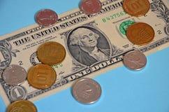 硬币1和2以色列人锡克尔和10 agorot谎言在一美国美元 纸钞票和硬币在蓝色背景 图库摄影