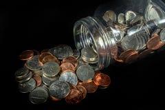 硬币从在黑背景的一个金属螺盖玻璃瓶溢出 免版税库存图片