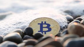 硬币bitcoin在海滩说谎 小波浪报道bitcoin bitcoin硬币在美丽的海石头说谎 股票录像