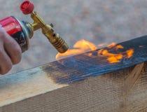 硬木木材对待与从煤气喷燃器的火 库存照片