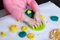 1.8硬盘驱动器 五岁的女孩坐在桌上,并且与颜色的戏剧在桌谎言测试,用工具加工,模子和面团装饰的 免版税库存图片