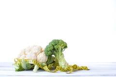 硬花甘蓝和花椰菜在一张木桌上与卷尺 库存图片
