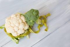 硬花甘蓝和花椰菜在一张木桌上与卷尺 免版税图库摄影