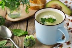 硬花甘蓝和鲕梨keramtcheskoy蓝色杯子汤在老木桌背景的 库存图片