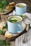 硬花甘蓝和鲕梨keramtcheskoy蓝色杯子汤在老木桌背景的 免版税库存照片