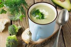 硬花甘蓝和鲕梨keramtcheskoy蓝色杯子汤在老木桌背景的 免版税图库摄影