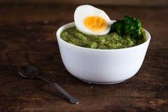 硬花甘蓝奶油色汤用在木背景的鸡蛋 免版税库存照片