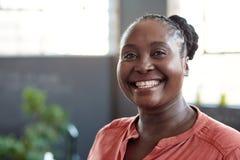 确信地微笑在办公室的年轻非洲女实业家 免版税库存图片