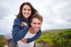 确信地微笑年轻的夫妇,当户外一起时 库存照片
