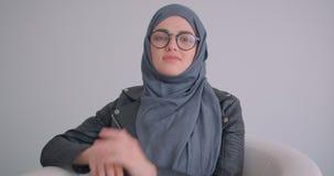 确信地看照相机的年轻可爱的回教女实业家和玻璃特写镜头画象hijab的户内 影视素材
