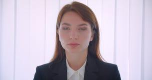 确信地看照相机的年轻成功的女实业家特写镜头画象户内在白色办公室 股票视频
