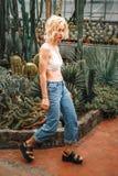 确信地走在多汁植物中的亭亭玉立的傲慢的女性模型 库存图片