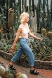 确信地走在多汁植物中的亭亭玉立的傲慢的女性模型 免版税库存照片
