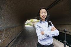 确信的亚裔女实业家常设胳膊画象横渡了在桥梁下 库存照片