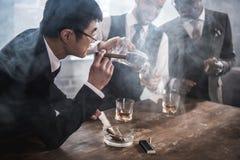 确信的亚洲商人抽烟的雪茄 图库摄影