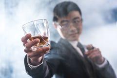 确信的亚洲商人饮用的威士忌酒和抽烟的雪茄 库存照片