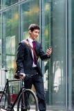 年轻确信的人谈话在手机在自行车commutin以后 免版税库存图片