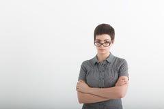确信的企业专家 看起来聪明的便衣的美丽的少妇保持胳膊横渡和严肃,当时 免版税图库摄影