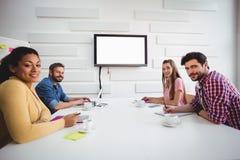 确信的伙伴画象在委员会会议期间在创造性的办公室 免版税图库摄影