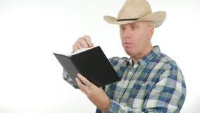 确信的农夫吃并且读了议程信息 库存图片