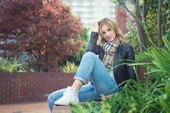 年轻确信的可爱的妇女坐的ouside 库存图片