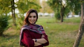 确信的女孩画象在时髦的围巾横渡的手上在照相机在公园 影视素材