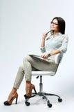年轻确信的女实业家坐与笔和片剂计算机的办公室椅子 库存照片