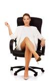 确信的女实业家坐扶手椅子 免版税库存照片