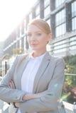 确信的女实业家常设胳膊画象横渡了外部办公楼 免版税库存图片