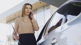 确信的女实业家谈话在有客户近的停放的汽车的智能手机 股票录像