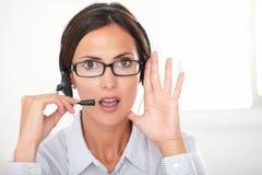 确信的女性执行委员交谈在耳机 图库摄影