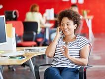 确信的女性设计师谈话在红色创造性的办公室空间的一个手机 库存照片