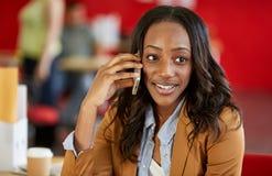 确信的女性设计师谈话在红色创造性的办公室空间的一个手机 免版税图库摄影