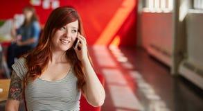确信的女性设计师谈话在红色创造性的办公室空间的一个手机 免版税库存照片