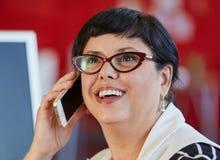 确信的女性设计师谈话在红色创造性的办公室空间的一个手机 库存图片