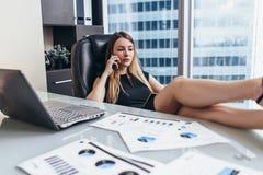 确信的女性首席执行官谈话在电话,当坐与她的脚在书桌在工作时 图库摄影