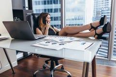 确信的女性首席执行官谈话在电话,当坐与她的脚在书桌在工作时 免版税库存照片
