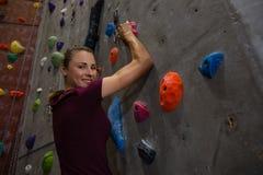 确信的女运动员上升的墙壁画象在健身房的 免版税库存图片