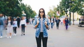 确信的小姐徒升定期流逝看照相机的太阳镜的站立在流程的繁忙的步行街道 股票录像