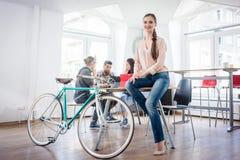 确信的少妇坐书桌在她的通勤者自行车附近 库存照片
