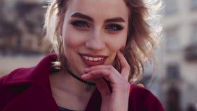 确信的少妇接触她的头发、面颊和份额往照相机的嬉戏的微笑 晴朗和刮风的天气 股票录像