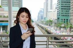 确信的年轻亚裔女商人在她的手上的注视着流动巧妙的电话都市大厦城市背景 图库摄影