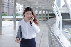 确信的年轻亚裔女商人谈话在电话,当走在现代城市时走道  库存图片